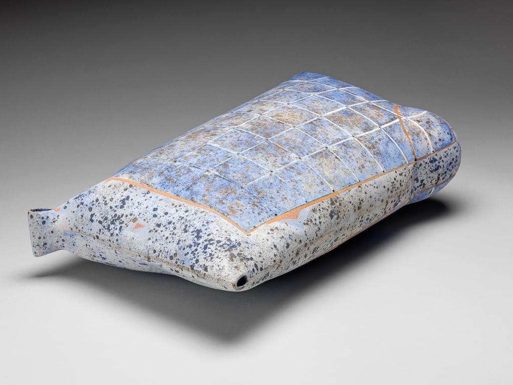An image of Studio Ceramics. Keeping a Secret. Heinz, Regina (b. Austria 1957). Sack-shaped ceramic form in stoneware, painted with glaze, dappled and chequered in pale brownish-orange, and blue, grey, and black. Of irregular sack shape, more rounded at the lower right corner, angular at top right, and having a folded strap on the top left corner (or vice versa if looked at from the other side). The sides are coated overall with a greyish-white glaze with greyish-black and black speckles, and decorated with a rectangle outlined in pale orange-brown, chequered with white lines with pin holes at the intersections, and dappled in blue. Across the rounded lower corner there is a diagonal line of pale orange-brown. Stoneware, hand-built, pierced, and decorated with lithium glaze, producing a speckled effect, slips, and oxides in pale brownish-orange, and shades of blue. Height, whole, 47.8 cm, width, top, 29.5 cm, width, bottom, 26.5 cm, depth, widest part, 14.4 cm, 2001. Given by Sir Nicholas and Lady Goodison through the National Art Collections Fund.