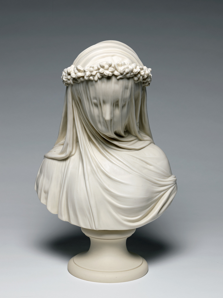 An image of The Bride. After Monti, Raffaelle (Italian, 1818-1881). Copeland Factory, Staffordshire, Stoke. Parian porcelain, slip cast. The circular socle is made separately and is held to the bust by a brass screw, nut, and washer. Height, whole, 38 cm, width, across shoulders, 23.3 cm, diameter, socle, 13.3 cm, 1873.