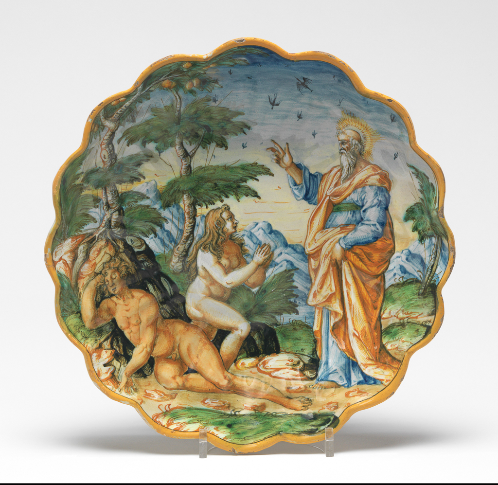 An image of Maiolica. The Creation of Eve. Shallow bowl on foot. Unknown maker, The Marches, Urbino. Adam sleeps on a mound below a fruit tree on the left. Eve rises from beside him with her hands held up in prayer, looking towards God, who stands to the right with his right hand raised. In the landscape background there are two more trees, mountains, and birds in the sky. The edge is yellow. The back is inscribed in the middle in dark blue, `Dio quado formo eva' (God when he formed Eve), the last word projecting outside the foot. Earthenware, moulded and tin-glazed overall; the glaze on the reverse is thinly applied and has a discoloured and speckled area on the right side. Painted in blue, green, yellow, orange, brown, black, and white. Height 8.0 cm, diameter 27.6 cm, circa 1575-1600. Renaissance. Notes: The design originated in a drawing by Federico Zuccaro/Zuccari (1540/1 - 1609), engraved by Johannes Sadeler I (1550-c. 1600), who was working in Italy during the 1590s.