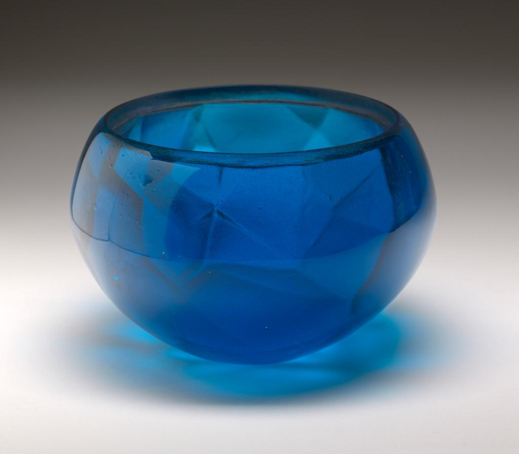 An image of Studio Glass/Cast Glass. Vessel. Cobalt Blue Agate Geode. Jarman, Angela (British, b. 1971). Cobalt blue lead crystal vessel, produced by lost wax casting, with mixed blue murrini cover. The vessel has a near-spherical shape with a wide mouth. The outside is polished; the interior is multifaceted with a rough surface; the walls are thick with an indented rim around the mouth to hold the insert; the underside is flat, circular and polished. The insert is a smooth, flat disc, with an off-centre circular hole, coloured with irregular, roughly concentric bands of fused opaque grey, blue, turquoise, pink and red glass. Between the bands and in the centre are wider areas of translucent cobalt blue glass, in which cell-like forms can be seen.  Lead crystal, cast and polished, with mixed blue murrini insert. Height, whole, 12.5 cm, diameter, 20 cm, 2017. Production Note: Murrini, glass mosaic that resembles agate stone, is characterised by fusing together differently coloured glass into concentric streaks, typically of purple and white. The process was known in Roman times and rediscovered by Venetian glass-makers in the 16th and 19th centuries. Acquisition Credit: Given by Nicholas and Judith Goodison through The Art Fund.