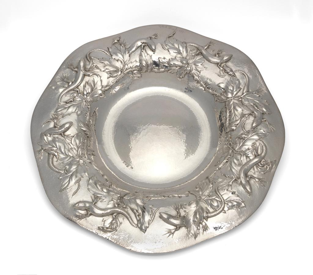 An image of Silver dish. Marks, Gilbert Leigh (British, 1861-1905). The dish was raised and the lizards and foliage embossed and chased. The lizards have a small piece of silver seamed under the jaw and neck, which allows the head to stand proud of the dish. The background to the dish is spot hammered. Height to rim 5 cm (variable), diameter (across rim) 42 cm, 1898-1899. Arts and Crafts movement.