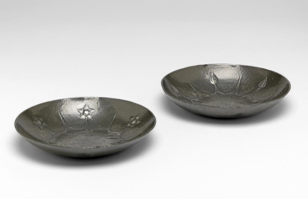 An image of Ashtray. Marks, Gilbert Leigh (British, 1861-1905). Pewter with lightly hammered surface, embossed with alternating flower heads and points radiating from a flower-shaped outline in the middle. Circular with curved sides. Height, 2 cm, width, 11.6 cm, 1900. Arts and Crafts. Victorian. Acquisition Credit: Given by Miss Ellen Bicknell.