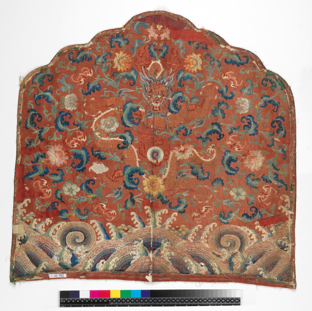 An image of Textiles. Throne back cushion cover. Unknown maker, China. Five-clawed dragon above waves, background pattern of peonies and bats. Satin; red ground. Metallic thread and silk embroidery - blues, greens, beiges, red, pink and grey; satin and stem stitch, couching. Height, whole, 60 cm, width, whole, 63 cm, circa 1775-circa 1780. Acquisition Credit: Given by Mrs. Soame Jenyns, in accordance with the wishes of her late husband, Soame Jenyns.
