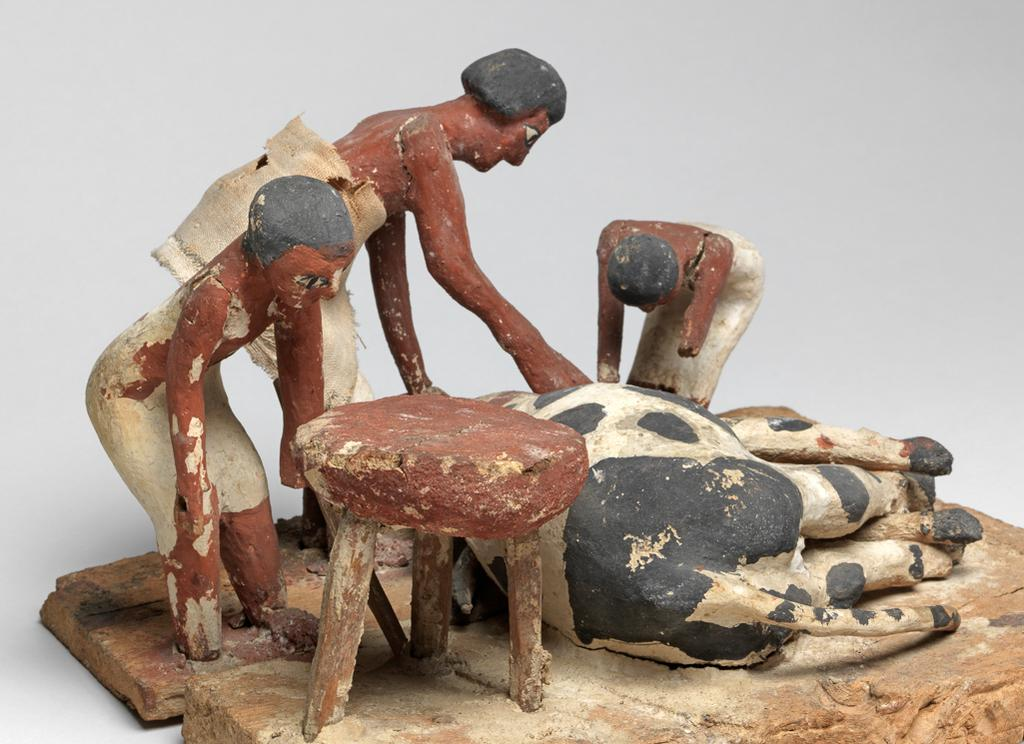 An image of Model. Butchers at work. Two men cut the throat of a bull lying on the ground; one man is cooking (?) under a tripod. A figure has been lost from one corner (only his feet remain). One figure has a cloth garment. Production Place: Egypt. Find Spot: Tomb of Khety, tomb 366 (Beni Hasan), Egypt. Painted wood, plaster and linen, height, 16 cm, length 29 cm, width 23 cm, circa 2010-circa 1950 B.C. Twelfth Dynasty, Middle Kingdom.