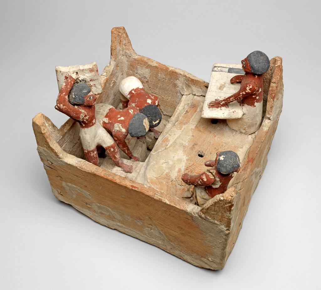 An image of Model of a granary: a square building with steps leading up to a platform. Two men prepare to lift a sack each: one man carries a sack up the steps; two men sit in the corners of the building - one is a scribe with writing board and palette on his knee. Plastered wood, painted yellow, red-brown (flesh), white and black. One man wears a cloth garment. Production Place: Egypt. Find Spot: Beni Hasan; tomb 366 (Khety). Wood, plaster, linen, painted, height 25 cm, length 29 cm, width 23.6 cm, circa 2010- circa 1950 B.C. Twelfth Dynasty; Middle Kingdom.