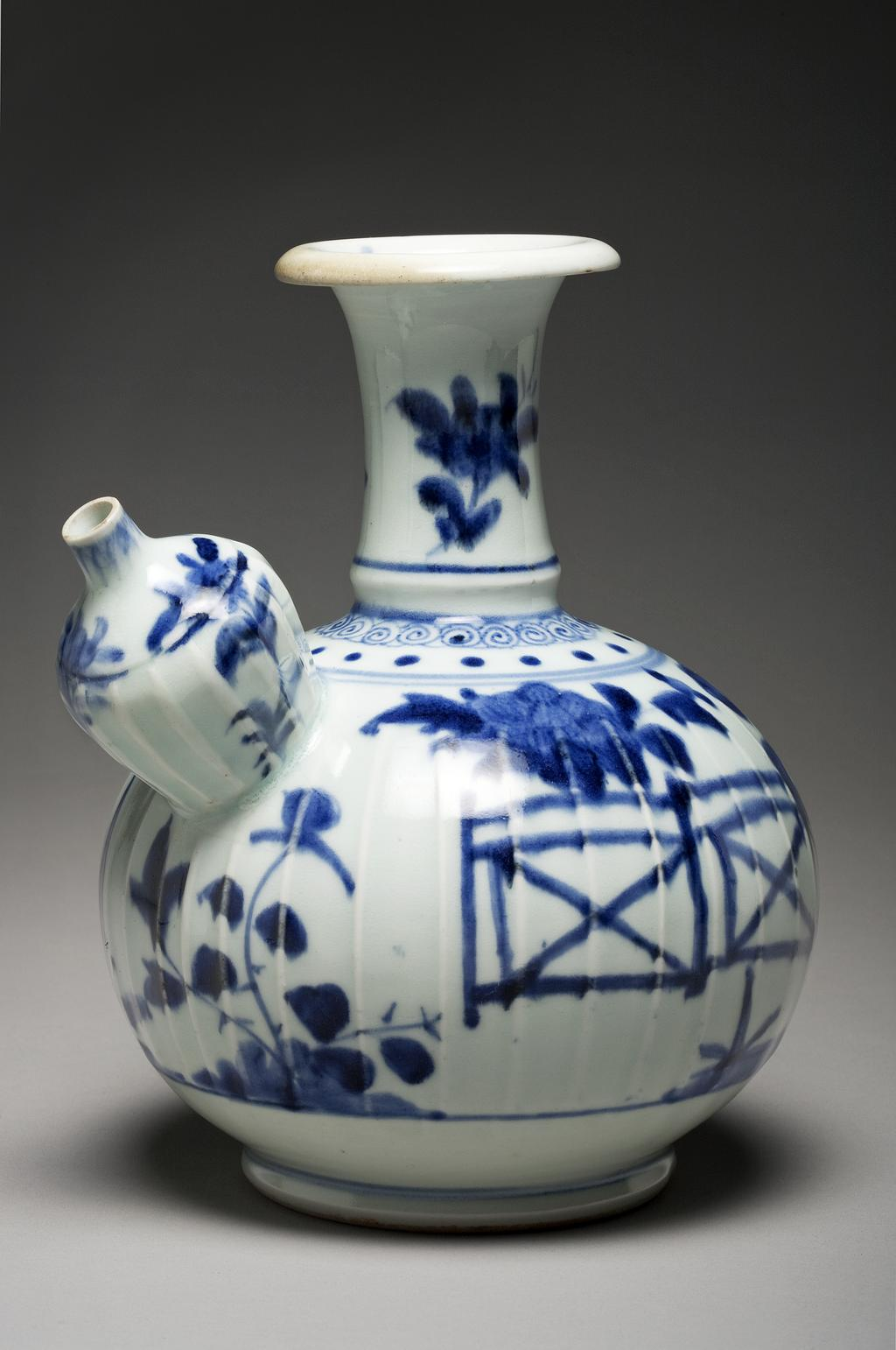 An image of Kendi Vessel. Hard-paste porcelain, moulded, assembled, and painted underglaze in blue with plants in a fenced garden, height 20.7 cm, circa 1700 to 1710. Japan.